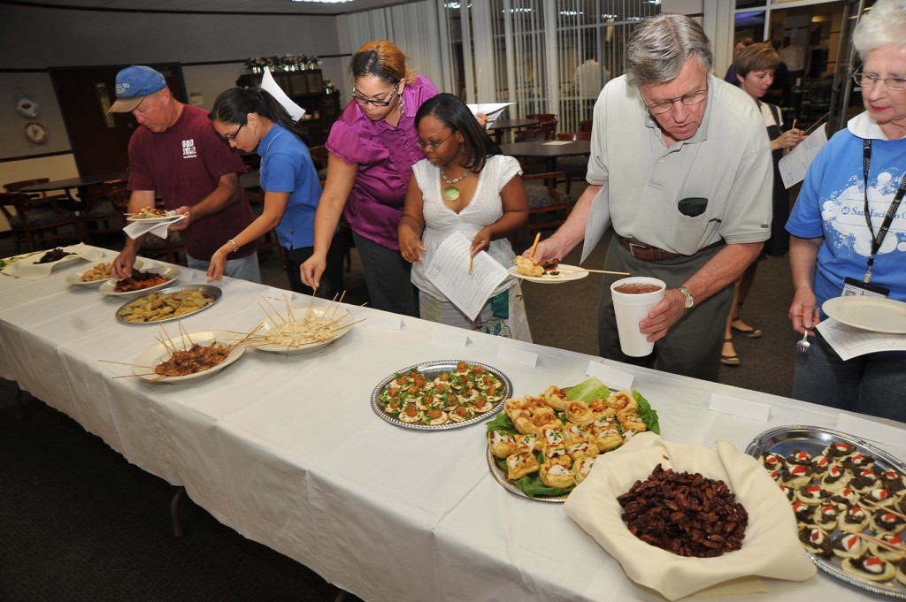 Students and faculty members sample appetizers prepared by culinary arts students.